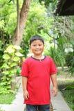 微笑在公园的逗人喜爱的亚裔男孩画象  库存图片