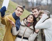 微笑在公园结合采取自画象通过手机 免版税库存图片