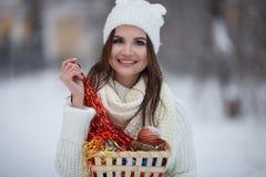 微笑在冬天森林里的女孩,下雪 免版税库存图片