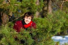 微笑在冬天森林里的年轻人 免版税库存图片