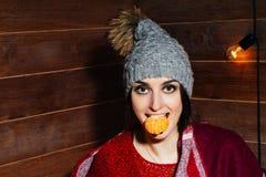 微笑在冬天衣裳和盖帽的年轻美丽的深色头发的妇女用蜜桔在木背景 免版税图库摄影