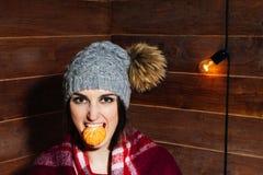微笑在冬天衣裳和盖帽的年轻美丽的深色头发的妇女用蜜桔在木背景 免版税库存照片