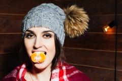 微笑在冬天衣裳和盖帽的年轻美丽的深色头发的妇女用蜜桔在木背景 库存图片