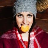微笑在冬天衣裳和盖帽的年轻美丽的深色头发的妇女用蜜桔在木背景 免版税库存图片