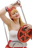微笑在减速火箭的样式的俏丽的女孩看一部16mm影片 免版税库存图片