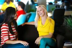微笑在创造性的设置的两位女性谈话和见面 库存照片