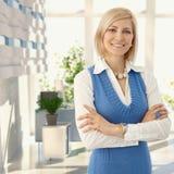 微笑在办公室的典雅的白肤金发的妇女 免版税库存图片