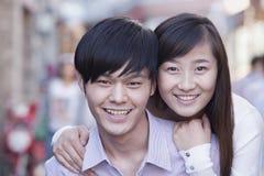 微笑在北京的年轻异性爱夫妇画象  免版税库存照片