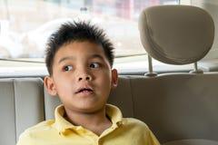 微笑在后座的亚裔男孩 免版税库存照片