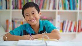 微笑在图书馆里的男性青春期前的学生 影视素材