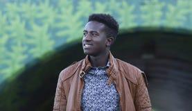 微笑在地下过道前面的英俊的年轻黑人 免版税库存图片