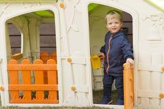 微笑在塑料房子窗口里的年轻男孩在操场 库存照片