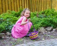微笑在复活节彩蛋狩猎期间的女孩 免版税库存图片