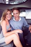 微笑在大型高级轿车的愉快的夫妇 免版税图库摄影