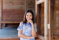 微笑在她的木家的一个泰国女孩 免版税库存图片