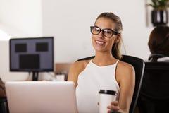 微笑在她起始的办公室的年轻企业家 库存照片