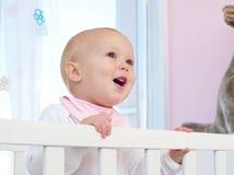 微笑在小儿床的一个愉快的婴孩的画象 免版税库存图片