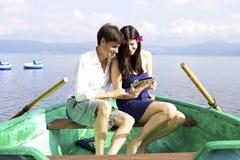 微笑在小船观看的ipad电子片剂的愉快的夫妇 免版税库存图片
