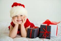 微笑在帽子圣诞老人的小女孩 免版税库存照片