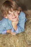 微笑在干草捆的年轻愉快的男孩 免版税库存照片
