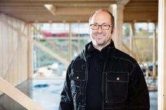 微笑在建造场所的确信的成熟木匠 免版税库存图片