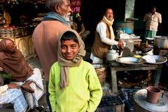 微笑在拥挤印地安室外咖啡馆的男孩 库存照片