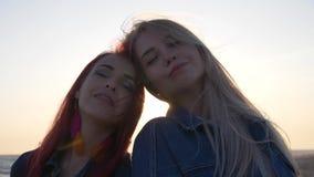 微笑在日落的背景中的女朋友风搅动他们的头发 影视素材