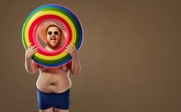 微笑在有一个可膨胀的圈子的泳装的厚实的滑稽的人 免版税库存图片