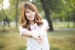 微笑在有棒棒糖的公园的年轻美丽的妇女画象  免版税图库摄影