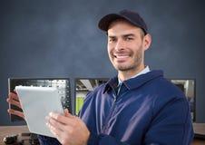 微笑在有片剂的计算机前面的治安警卫 免版税库存照片