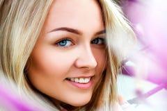微笑在桃红色开花的花附近的秀丽年轻金发碧眼的女人 免版税图库摄影