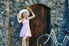 微笑在桃红色礼服,草帽的女孩摆在画象,站立在织地不很细石头、老墙壁和木门附近 免版税库存照片