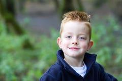 微笑在森林的小男孩 免版税库存图片