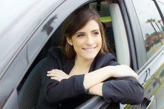 微笑在汽车里面的逗人喜爱的愉快的女商人 免版税库存照片