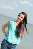微笑在海的美丽的女孩 免版税图库摄影