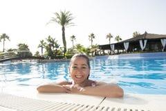 微笑在游泳池的愉快的拉丁妇女 免版税库存照片