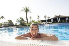 微笑在游泳池的愉快的拉丁妇女 免版税库存图片