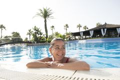 微笑在游泳池的愉快的拉丁妇女 库存照片