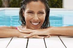 微笑在游泳池边的俏丽的妇女 库存图片