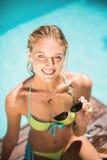 微笑在游泳池边附近的美丽的妇女画象 库存照片