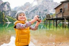 微笑在湖Bries和使用与照相机的年轻白肤金发的女孩 免版税库存图片