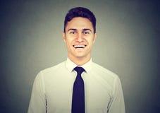 微笑在灰色背景的英俊的年轻人 免版税库存图片