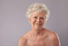 微笑在灰色背景的资深妇女 免版税库存图片