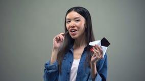微笑在照相机的可爱的亚裔女孩吃黑暗的巧克力,广告 股票录像