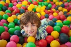 微笑在球水池的逗人喜爱的男孩 图库摄影