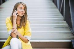 微笑在电话的快乐的女实业家 免版税库存照片