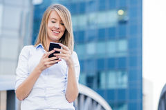 微笑在电话的快乐的女实业家 免版税库存图片