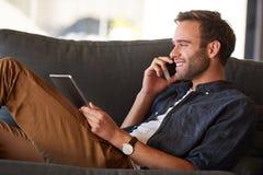 微笑在电话的愉快的cucasian人,当拿着片剂时 免版税库存照片