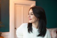 微笑在白色毛线衣的美女,看  免版税库存图片