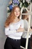 微笑在白色的红发,亲切的女孩在花和镜子附近穿衣 库存照片